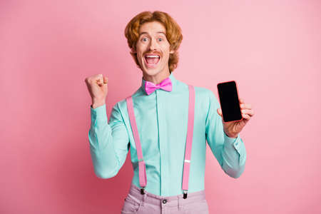 Photo of young happy joyful excited crazy cheerful positive happy man win smartphone isolated on pink color background