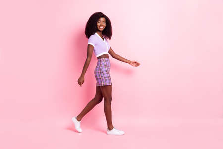 Full length body size profile side view of attractive cheerful thin girl walking isolated over pink pastel color background