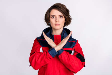 Photo of young serious woman paramedic crossed hands show no stop denial sign isolated over white color background