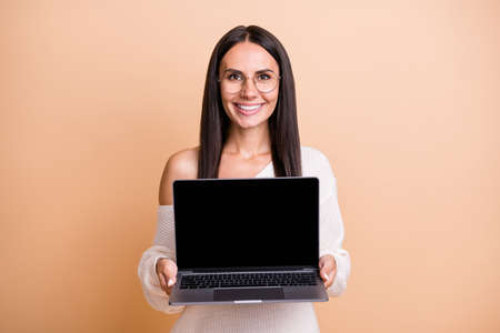 Photo of young cheerful woman present show laptop recommend advert isolated over beige color background