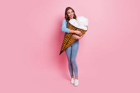 Full length body size view of attractive cheerful girl holding in hands hugging big paper icecream isolated over pink pastel color background
