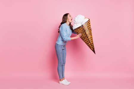 Full size photo of young beautiful happy excited crazy girl eating huge ice cream isolated on pink color background