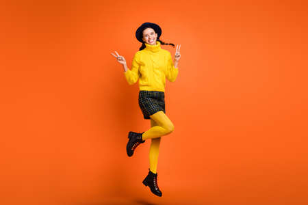 Full length body size view of pretty cheerful girl jumping showing v-sign having fun isolated over bright orange color background