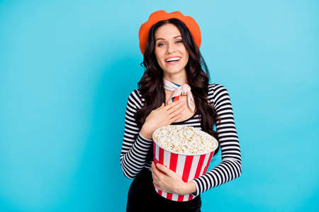 Photo of young attractive girl happy positive smile excited laugh watch movie eat popcorn isolated over blue color background
