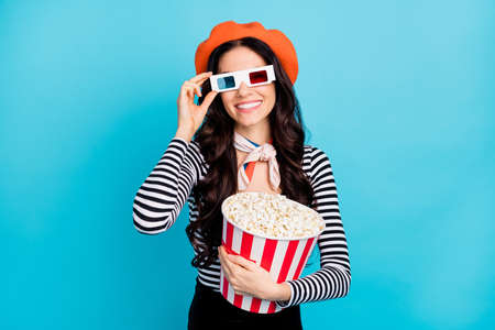 Photo of young girl happy positive smile hold popcorn box wear 3d glasses watch film comedy isolated over blue color background