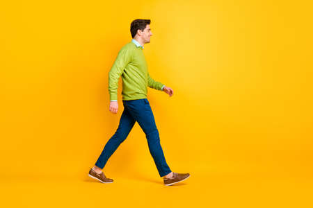 Full length body size profile side view of content cheerful guy it specialist geek walking isolated over bright yellow color background