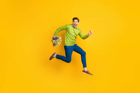 Full length body size profile side view of nice cheery crazy guy jumping running carrying flowers floristry isolated on vivid yellow color background