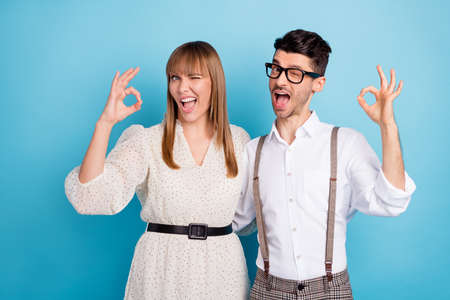Photo of excited flirty two persons dressed white clothes winking showing okey isolated blue color background