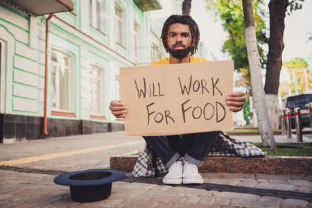 Photo portrait of hungry man demonstrating carton table looking for job will work for food sitting on ground near black hat for money