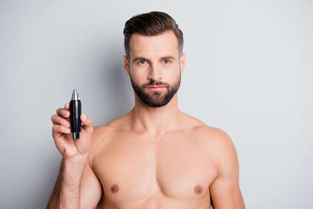 Photo of young handsome man serious hold hand electric hair cutter trimmer isolated over grey color background