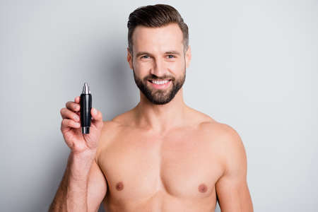 Photo of young handsome man happy positive smile hold electric machine hair remove isolated over grey color background
