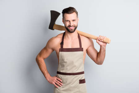 Portrait of attractive cheerful guy butcher wear apron carrying wooden ax on shoulder isolated over light grey color background