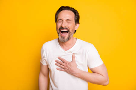Photo of happy funky mature man laugh good mood joke hold hand chest isolated on yellow color background
