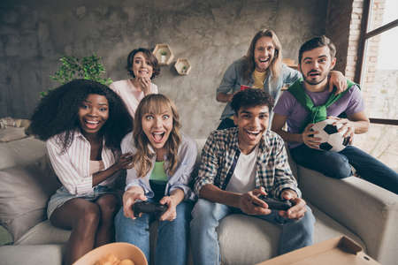 Portrait of attractive cheerful friends sitting on sofa having fun playing video game in house loft brick style interior indoors Stockfoto