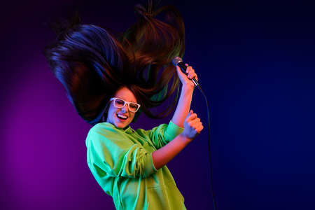 Photo of cheerful happy young woman fly hair raise mic pop star isolated on neon purple color background