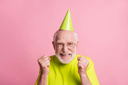 Close up portrait of hooray pensioner hands fists wear birthday hat spectacles green color t-shirt isolated on pastel pink color background