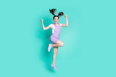 Full length photo of funny cheerful girl jump wind tails raise knee wear violet short overall footwear isolated turquoise color background