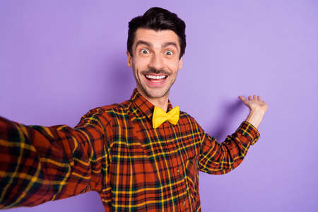 Photo of positive young guy shoot selfie hand showing empty space wear bow tie plaid shirt isolated violet background