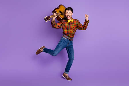 Photo of funky crazy musician guy hold guitar dance wear bow tie plaid shirt jeans shoes isolated purple background
