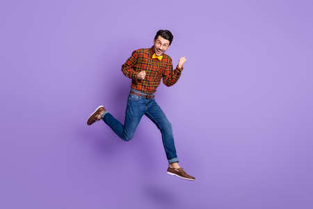 Full size photo of young handsome cheerful smiling positive man jumping in victory isolated on violet color background Standard-Bild