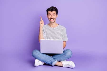 Photo of guy sit floor raise finger hold netbook shiny smile wear white t-shirt jeans sneakers isolated purple background