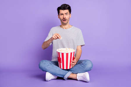 Photo of guy hold popcorn box scared open mouth wear striped white t-shirt jeans sneakers isolated violet background