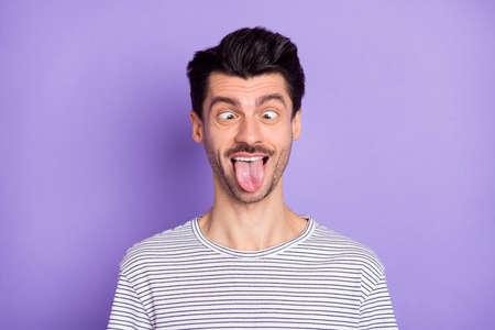 Portrait of nice attractive crazy foolish cheerful guy grimacing having fun isolated over bright violet purple color background