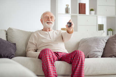 Photo of aged man pensioner happy positive smile sit couch home watch tv cinema switch channel remote controller Foto de archivo