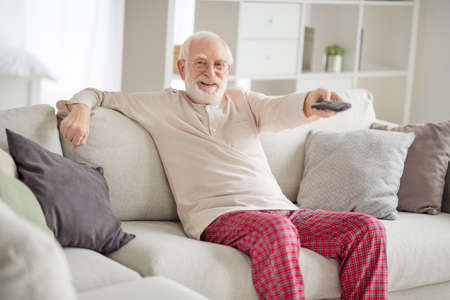Photo of elderly man happy positive smile sit sofa house have fun watch television switch channel remote controller