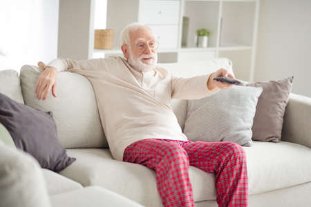 Photo of aged man pensioner sit couch home rest relax look watch tv cinema switch channel remote controller