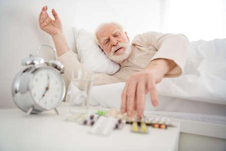 Photo of senior man pensioner lie bad rest home indoors unwell unhealthy look meds pills painkiller Imagens