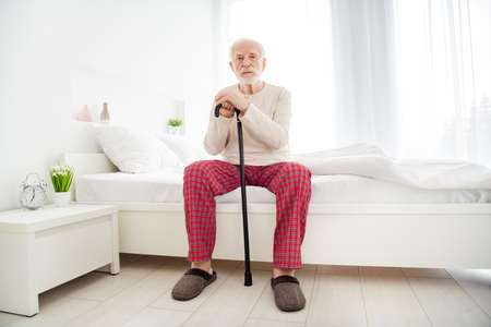 Full body photo of aged man pensioner unhappy sad upset alone think sit bad home indoors hold walking stick Imagens