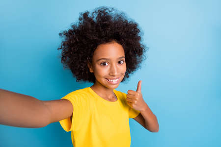 Photo of brunette little afro american girl wear yellow t-shirt take selfie make thumb up isolated on blue color background