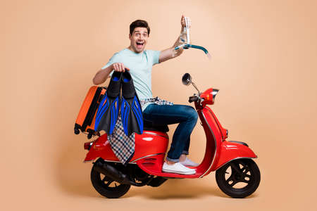 Profile side view portrait of nice cheerful guy sitting on moped carrying diving tools ocean destination isolated over beige pastel color background