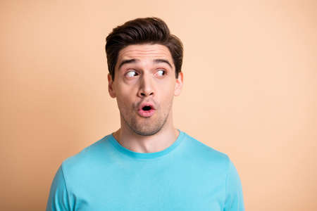 Close-up portrait of attractive worried guy looking aside copy space wow isolated over beige pastel color background