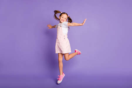 Full length of carefree happy small girl wear pink dress raise hands good mood isolated on violet color background