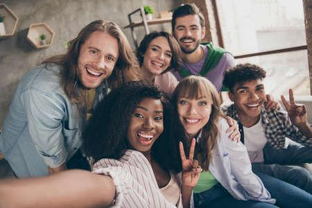 Photo portrait of smiling students showing v-sign gestures taking selfie sitting on sofa embracing together