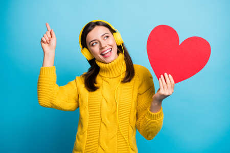Portrait of nice cute cheerful girl holding in hand heart shape listening single having fun isolated over vivid blue color background
