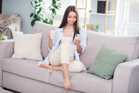 Full size photo of nice optimistic brunette long hairdo lady sit on coach drink look telephone wear blue shirt at home