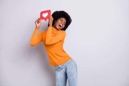 Photo of young black woman happy positive smile hold heart like reaction icon click popular isolated over grey color background Foto de archivo