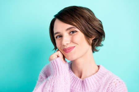 Photo of adorable pretty young woman wear violet sweater arm cheek smiling isolated turquoise color background Stock Photo