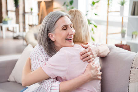 Photo of happy charming cheerful young woman and old lady hug love family indoors inside house home