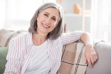 Photo of happy cheerful old pretty lady sit couch smile good mood smile indoors inside house home apartment