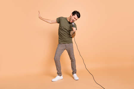 Full size photo of hooray brunet guy sing in mic wear t-shirt trousers sneakers isolated on beige color background Reklamní fotografie