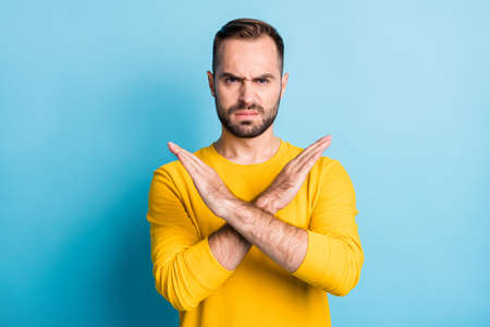 Photo of young handsome serious unhappy man in yellow sweater showing no sign crossed hands isolated on blue color background
