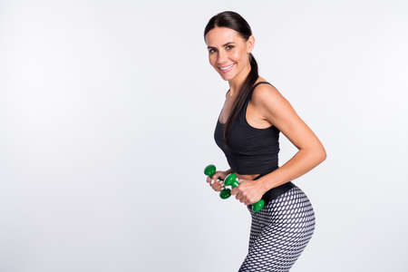 Profile side photo of happy young woman stand copyspace hold dumbbells biceps exercise isolated on grey color background