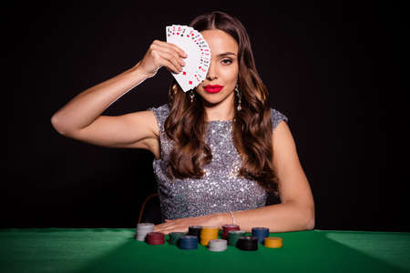 Photo of serious stunning young woman hold cards cover face sit poker table player isolated on black color background