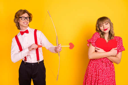 Photo portrait of guy with arrow bow and funky girl fell in love embracing red heart isolated on vivid yellow background
