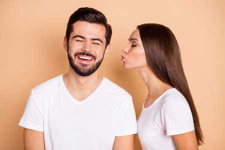 Photo of pretty shiny married couple dressed white t-shirts kissing cheek closed eyes isolated beige color background Stock Photo