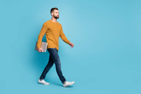 Full length body size view of attractive guy wearing casual going carrying laptop copy space isolated over bright blue color background